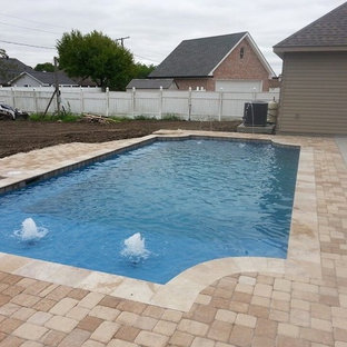 Design ideas for an arts and crafts custom-shaped pool in New Orleans with a water feature and natural stone pavers.