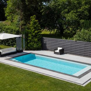 Immagine di una piscina monocorsia moderna rettangolare di medie dimensioni con pavimentazioni in pietra naturale
