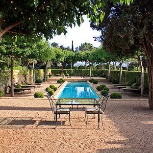 Diseño de piscina alargada, mediterránea, rectangular, en patio, con granito descompuesto