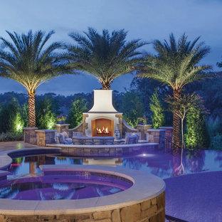 Ejemplo de piscinas y jacuzzis infinitos, tropicales, grandes, a medida, en patio trasero, con adoquines de piedra natural