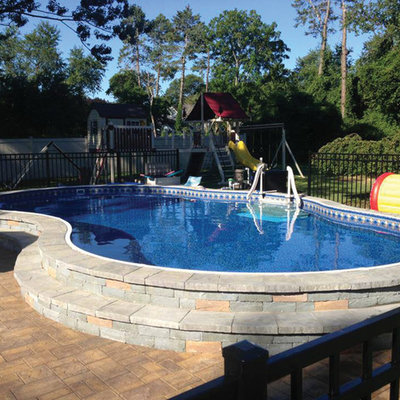 Example of a mid-sized classic backyard stone and custom-shaped aboveground pool design in Detroit