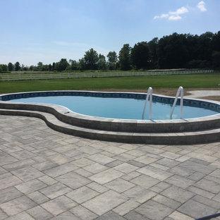 Foto de piscina alargada, tradicional, pequeña, tipo riñón, en patio trasero, con suelo de hormigón estampado
