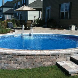 Ejemplo de piscina elevada, clásica, de tamaño medio, a medida, en patio trasero, con adoquines de ladrillo