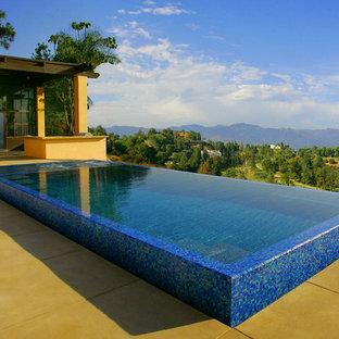 Mittelgroßer Moderner Infinity-Pool hinter dem Haus in rechteckiger Form mit Wasserspiel und Betonplatten in Los Angeles