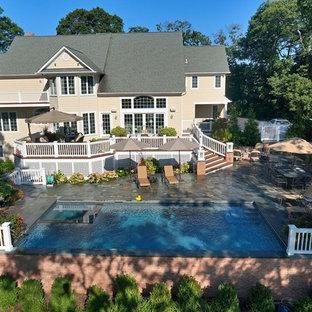 Modelo de piscinas y jacuzzis alargados, tradicionales, de tamaño medio, en forma de L, en patio trasero, con adoquines de piedra natural