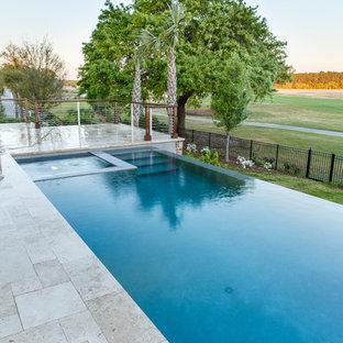 Foto de piscinas y jacuzzis infinitos, contemporáneos, de tamaño medio, rectangulares, en patio trasero, con adoquines de piedra natural