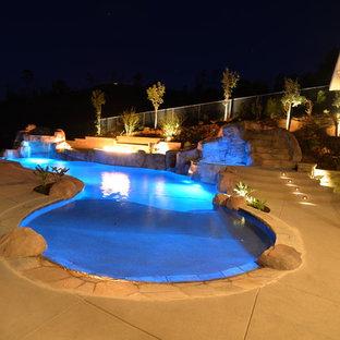Idee per una grande piscina tradizionale personalizzata dietro casa con un acquascivolo e pavimentazioni in cemento