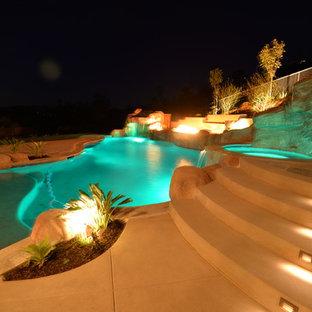 Imagen de piscina con tobogán clásica renovada, grande, a medida, en patio trasero, con adoquines de hormigón