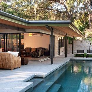 タンパのミッドセンチュリースタイルのおしゃれな裏庭プールの写真