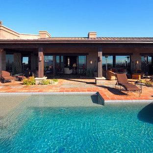 Diseño de piscinas y jacuzzis retro, grandes, a medida, en patio trasero, con suelo de baldosas