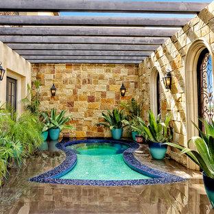 Ejemplo de piscinas y jacuzzis mediterráneos, extra grandes, a medida, en patio, con suelo de baldosas