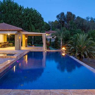 Imagen de casa de la piscina y piscina infinita, mediterránea, grande, rectangular, en patio trasero, con suelo de baldosas