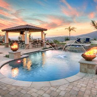 Foto de piscina con fuente alargada, mediterránea, a medida, en patio trasero, con adoquines de piedra natural