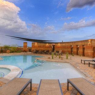 На фото: с высоким бюджетом спортивные бассейны произвольной формы в стиле фьюжн с мощением тротуарной плиткой и джакузи