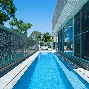 Modelo de piscina alargada, contemporánea, rectangular, en patio lateral, con suelo de baldosas