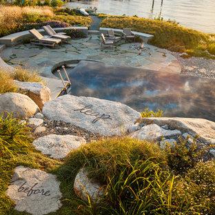 Coastal backyard stone and rectangular infinity pool photo in Seattle