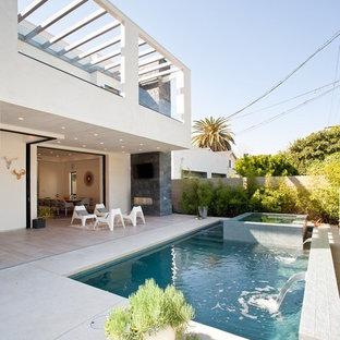 Foto de piscina con fuente minimalista, pequeña, rectangular, en patio trasero, con losas de hormigón