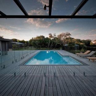 Modelo de piscina alargada, actual, grande, en forma de L, en patio trasero, con entablado