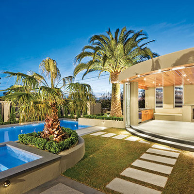 Inspiration for a large mediterranean backyard concrete paver and rectangular lap hot tub remodel in Orange County