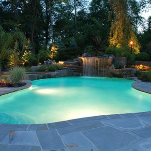 Mid-sized island style backyard stone and custom-shaped lap pool fountain photo in Charlotte