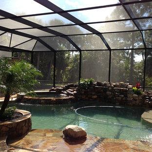 Idee per una grande piscina coperta naturale tropicale personalizzata con una dépendance a bordo piscina e pavimentazioni in pietra naturale