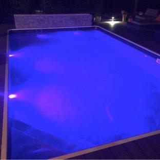 Idee per una grande piscina fuori terra moderna rettangolare dietro casa con pedane e fontane