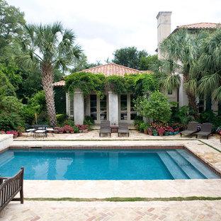 Удачное сочетание для дизайна помещения: прямоугольный, спортивный бассейн среднего размера на заднем дворе в средиземноморском стиле с покрытием из каменной брусчатки и джакузи - самое интересное для вас