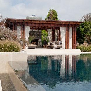 Ejemplo de piscinas y jacuzzis infinitos, minimalistas, de tamaño medio, rectangulares, en patio trasero, con adoquines de piedra natural