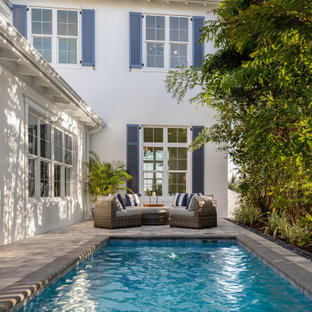 Inspiration for a mid-sized beach style backyard rectangular natural pool in Tampa with with privacy feature and concrete pavers.