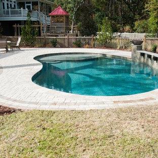 Immagine di un'ampia piscina monocorsia classica personalizzata dietro casa con fontane e pavimentazioni in pietra naturale