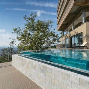 Diseño de piscina infinita, contemporánea, de tamaño medio, rectangular, en azotea, con adoquines de piedra natural