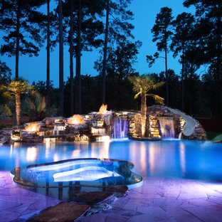 Photo of an expansive tropical backyard custom-shaped natural pool in New Orleans with natural stone pavers and a hot tub.