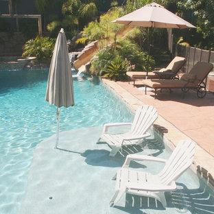 Ejemplo de piscina con tobogán alargada, tropical, de tamaño medio, a medida, en patio trasero, con adoquines de piedra natural