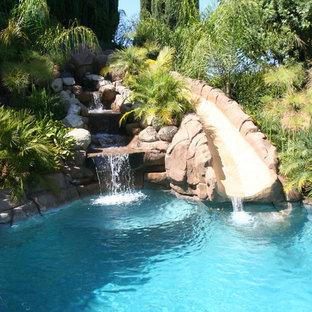 Modelo de piscina con tobogán alargada, tropical, de tamaño medio, a medida, en patio trasero, con adoquines de piedra natural