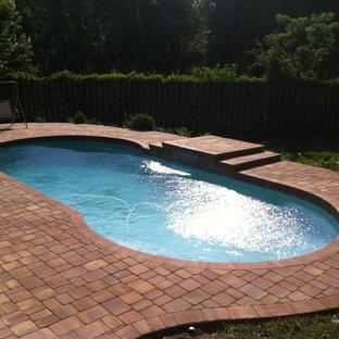 Modelo de piscina clásica, de tamaño medio, a medida, en patio trasero, con adoquines de ladrillo