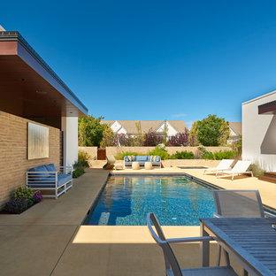 Ejemplo de piscina moderna, de tamaño medio, rectangular, en patio, con losas de hormigón