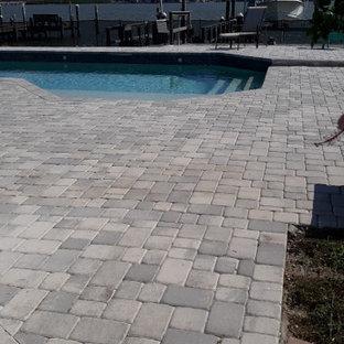 Ejemplo de piscina actual, de tamaño medio, rectangular, en patio trasero, con adoquines de ladrillo