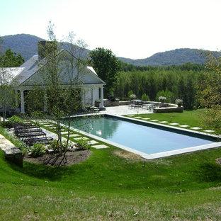 Imagen de casa de la piscina y piscina natural, ecléctica, grande, rectangular, en patio lateral, con adoquines de piedra natural