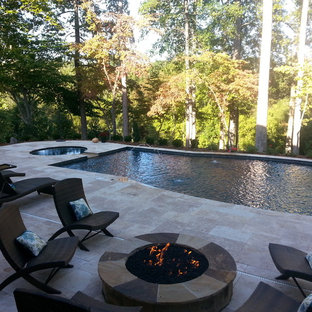 This is an example of a mid-sized transitional backyard rectangular lap pool in Charlotte with natural stone pavers and a hot tub.