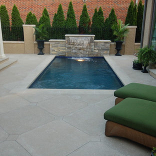 Photo of a small arts and crafts courtyard rectangular lap pool in Other with a water feature and concrete pavers.