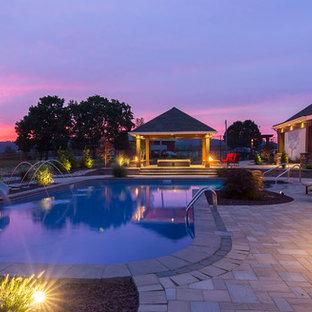 """Ispirazione per una grande piscina monocorsia design a """"L"""" dietro casa con un acquascivolo e pavimentazioni in cemento"""