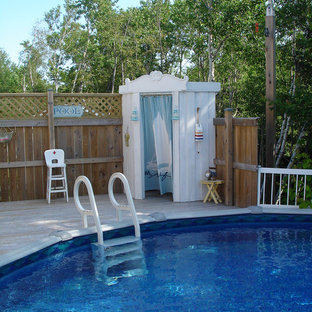Nautical round swimming pool in Other with decking and a pool house.