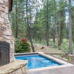 Imagen de piscina alargada, rústica, pequeña, rectangular, en patio trasero, con losas de hormigón