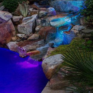 Ispirazione per una grande piscina naturale boho chic personalizzata dietro casa con fontane e pavimentazioni in pietra naturale