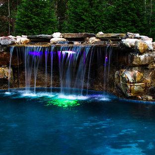 Ejemplo de piscina con fuente natural, ecléctica, grande, a medida, en patio trasero, con adoquines de piedra natural