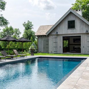 Inspiration for a large country backyard rectangular lap pool in New York with a pool house and natural stone pavers.