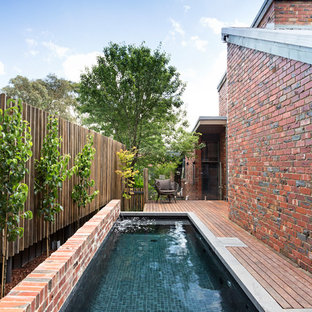 Small contemporary rectangular swimming pool in Melbourne with a water feature and decking.
