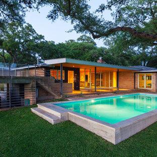 Modelo de piscina alargada, vintage, grande, rectangular, en patio trasero, con losas de hormigón