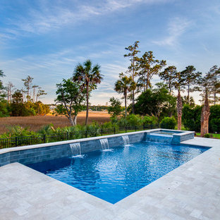 This is an example of a mid-sized contemporary backyard rectangular natural pool in Charleston with natural stone pavers and a hot tub.