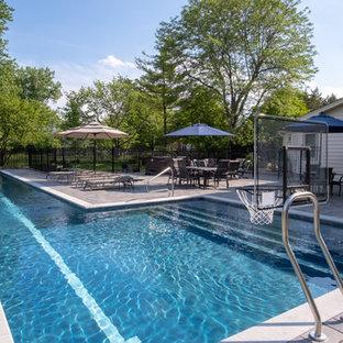 Foto de piscina alargada, tradicional, grande, en forma de L, en patio trasero, con adoquines de hormigón